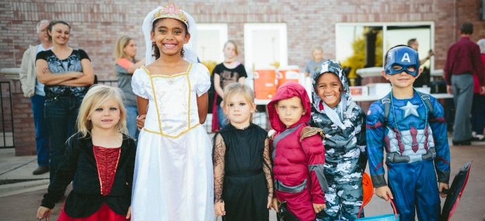 A photo (by Conner Baker on Unsplash) of kids in various Halloween costumes