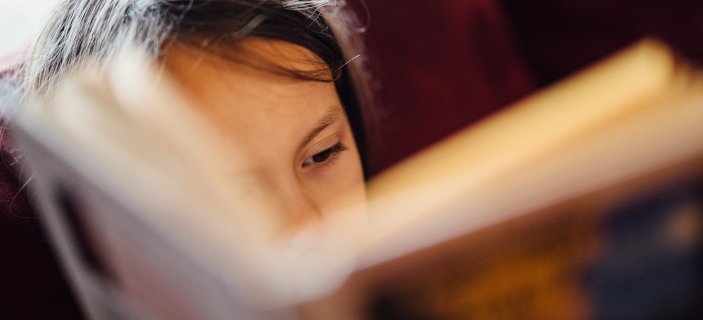A photo (by Johnny McClung - Unsplash) of a child reading a book