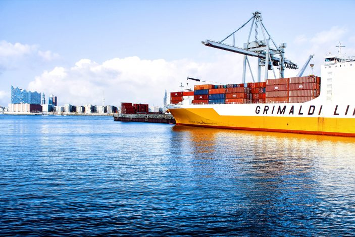 Photo (by Axel Ahoi on Unsplash) of a cargo ship