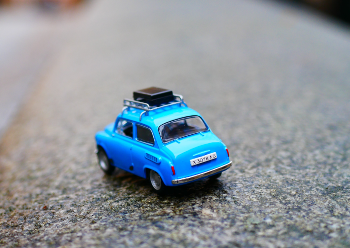 A photo (by Karine Germain, Unsplash) of a toy car loaded with luggage