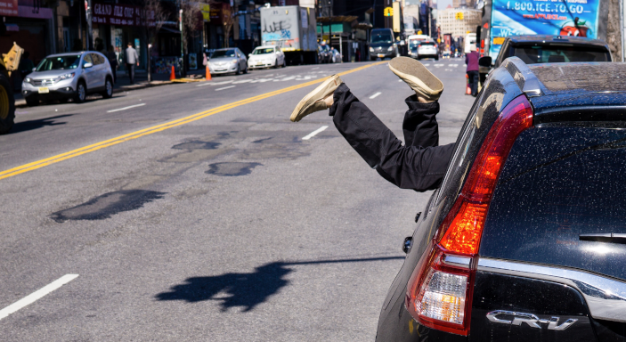 A photo (by Ben Stern, Unsplash) of a person's legs hanging out of a car window - used to illustrate the bored children feel on long car journeys!