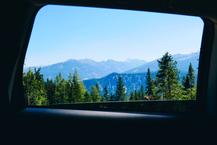 A photo (by Paul Herman, Unsplash) of trees and mountains viewed through a car window - used to illustrate cheap family travel games