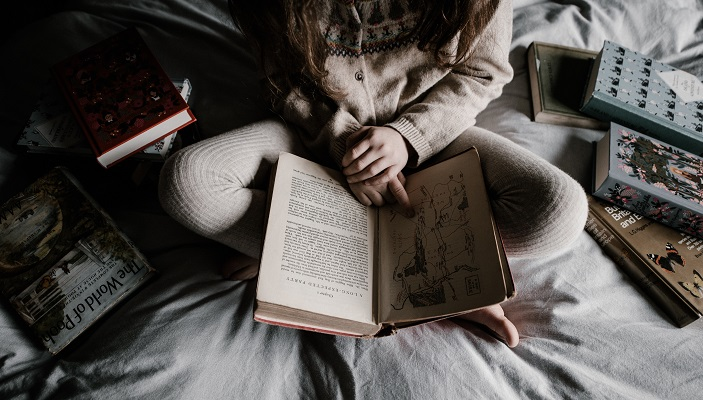 A photo (by Annie Spratt, Unsplash) of a child, sitting on a bed surrounded by books