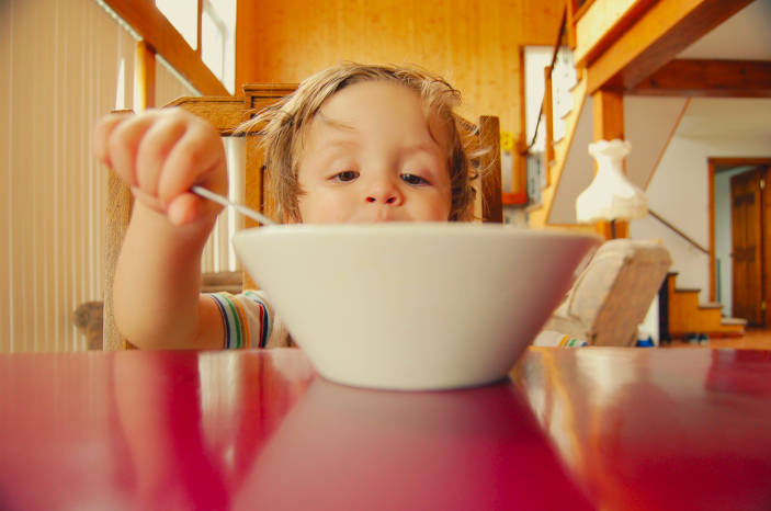 A photograph (by Hal Gatewood on Unsplash) of a child eating from a bowl