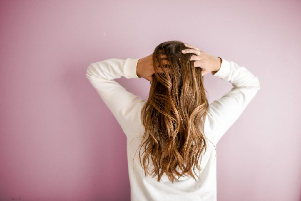 A photo of a woman, viewed from behind, with long hair - used to illustrate ways to make extra money, by selling your hair