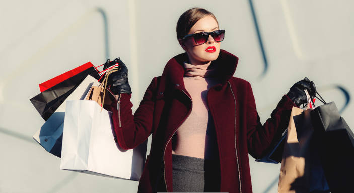 A photo (by freestocks.org on Unsplash) of a woman, wearing sunglasses carrying shopping bags