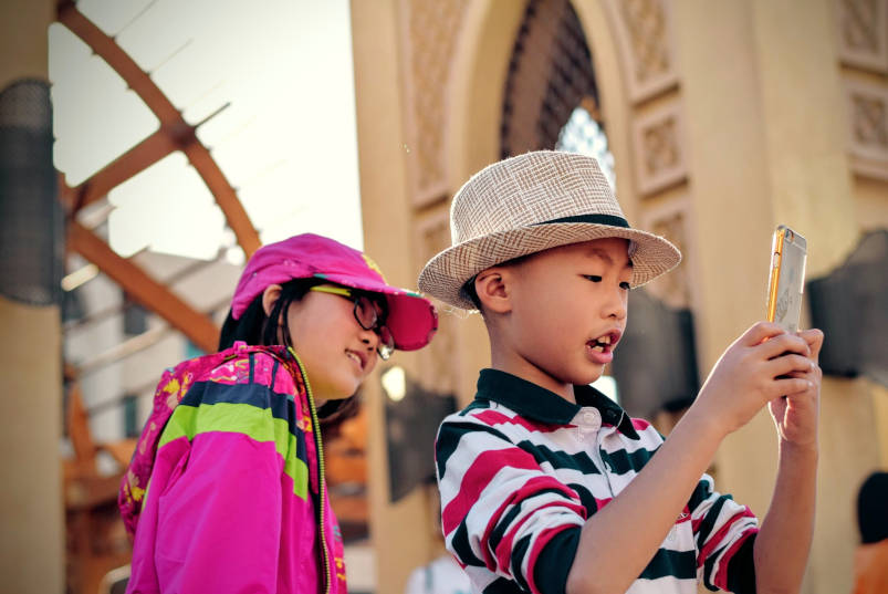 A photo (by Tim Gouw on Unsplash) of two kids - one holding a mobile phone, playing a game, as the other watches