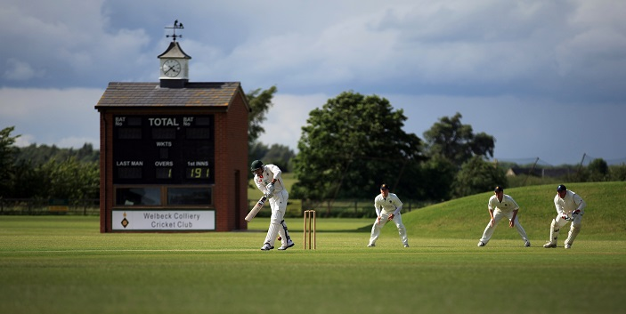 A photograph (from Craig Hughes, Unsplash) of people playing cricket