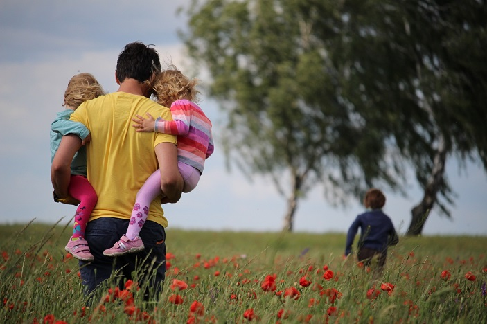 A father carries two children through a field of poppies whilst a third child runs in the distance