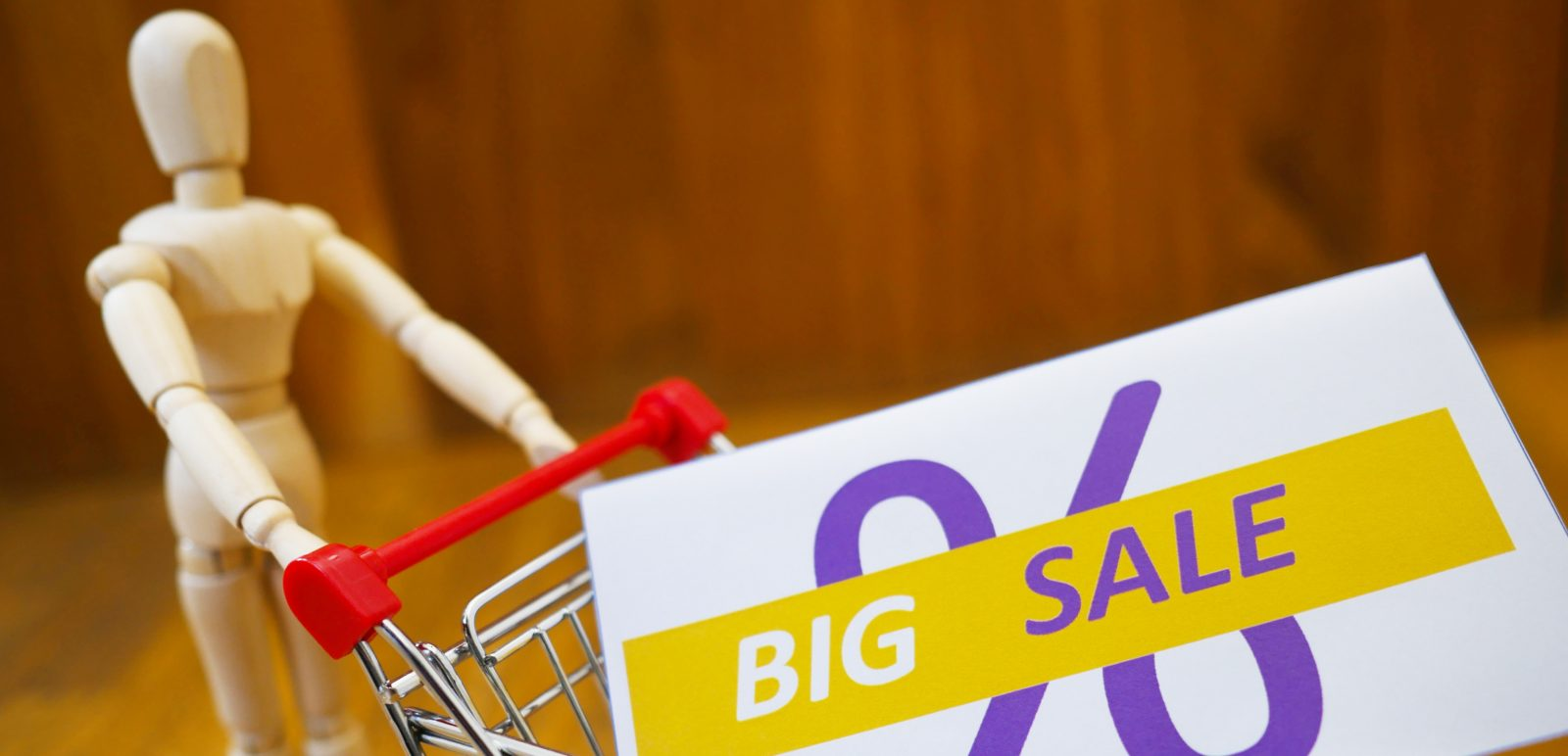 A photo (by Mein Deal on Unsplash) of a wooden mannequin pushing a shopping trolley