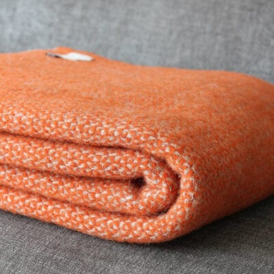 A woollen orange throw rug or blanket, from Not On The Highstreet