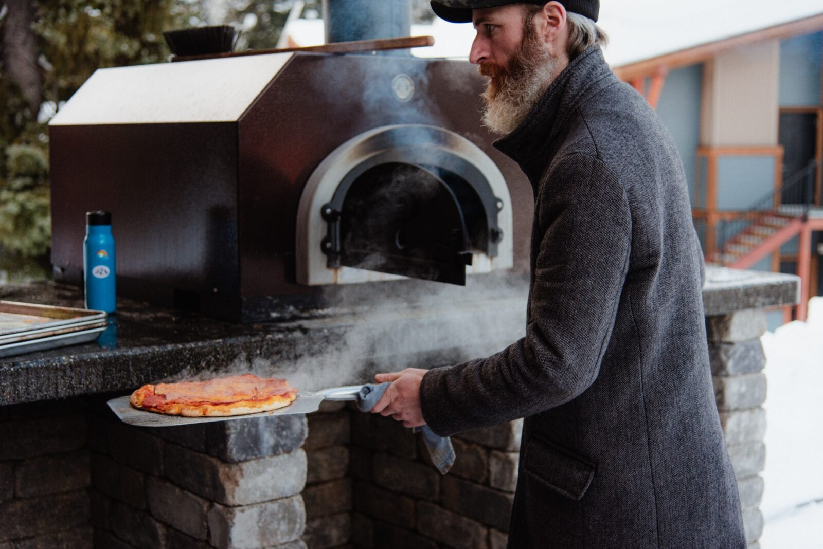 A man removing a freshly cooked delicious pizza from a pizza oven in his garden